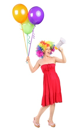 Full length portrait of a woman yelling via a loudspeaker and holding balloons isolated on white background Stock Photo - 10453716