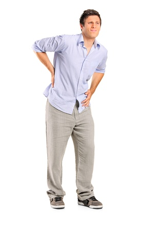 exhausted: Full length portrait of a young man suffering from a back pain isolated on white background Stock Photo