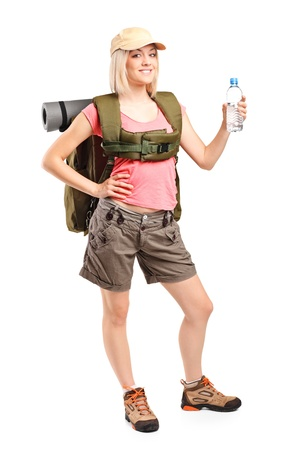 standing water: Full length portrait of a woman hiker with backpack holding a bottle of water isolated on white background