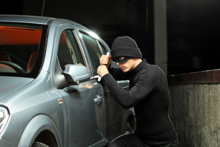 robo de autos: Un ladrón con una máscara de robo tratando de robar un automóvil
