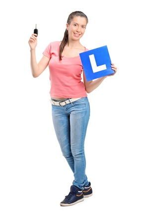 l hand: Happy teenager holding a car key and L plate isolated against white background Stock Photo