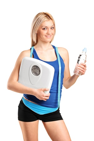 scale model: An athlete female holding a weight scale and bottle of water isolated on white background Stock Photo