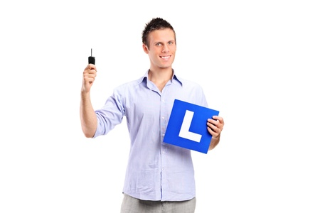 learner: Happy man holding a car key and L plate isolated against white background Stock Photo