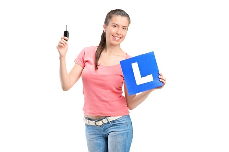 l plate: Happy teenager holding a L plate and a car key isolated on white background