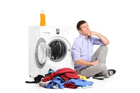 thinking machine: Hombre pensativo joven sentado al lado de una lavadora aisladas contra el fondo blanco