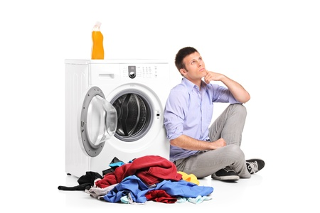 man laundry: Thoughtful young male sitting next to a washing machine isolated against white background