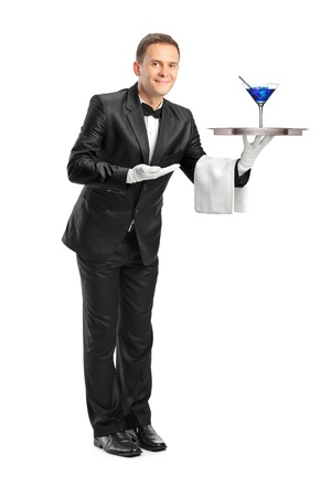 Full length portrait of a butler with bow tie carrying a tray with a cocktail on it isolated against white background photo
