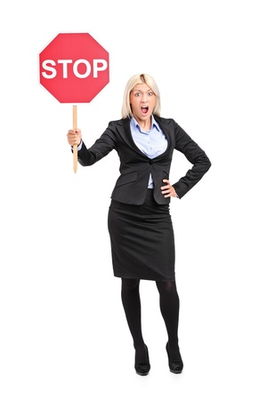 Full length portrait of a young businesswoman holding a traffic sign stop isolated on white background photo