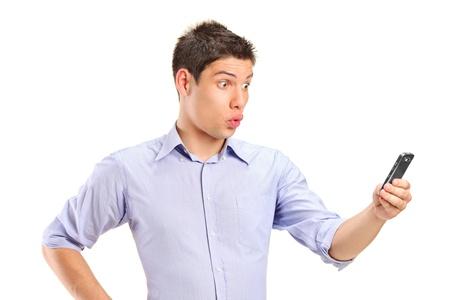 cara sorpresa: Un hombre confundido joven que busca en el tel�fono m�vil aisladas sobre fondo blanco