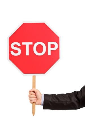 A hand holding a traffic sign stop isolated against white background photo