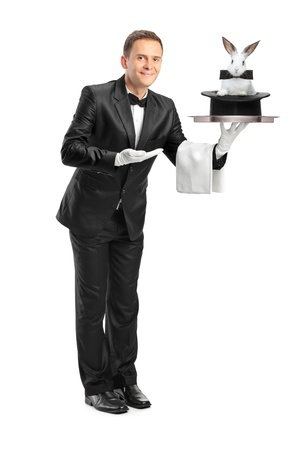 Full length portrait of a butler carrying a tray with a rabbit in a hat on it isolated on white background photo