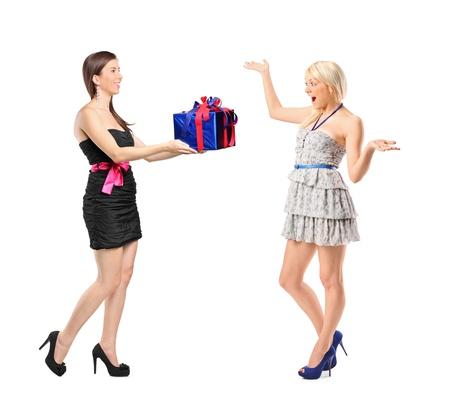 dar un regalo: Retrato de longitud completa de una niña con un regalo y una mujer sorprendida aisladas sobre fondo blanco Foto de archivo
