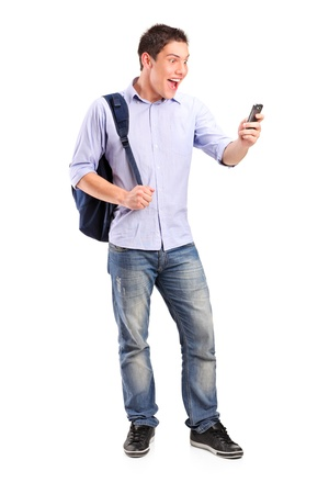 Full length portrait of a smiling young man looking at a cell phone isolated on white background photo