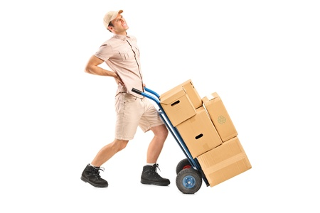 dorsalgia: Full length portrait of a delivery boy, suffering from a back pain, pushing a hand truck isolated on white background
