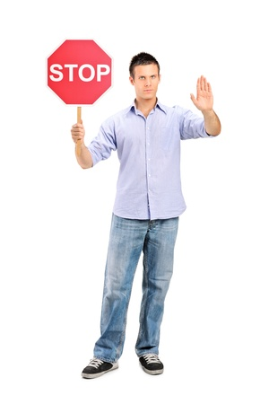 Full length portrait of a man gesturing and holding a traffic sign stop isolated on white background photo