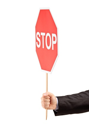 Hand holding a traffic sign stop isolated against white background Stock Photo - 10844293