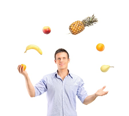 juggling: Smiling handsome man juggling fruits isolated on white background