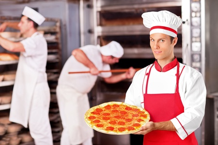 pizza oven: A male baker holding freshly baked pizza in bakery