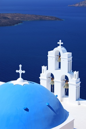 Blue dome Church St. Spirou in Firostefani on the island of Santorini Greece, overlooking the sea photo