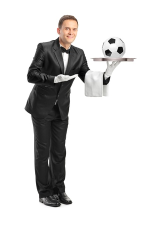 Full length portrait of a butler with bow tie holding a tray with a football on it isolated against white background photo