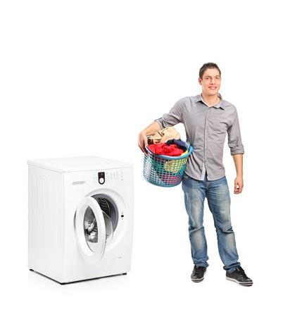 Full length portrait of a smiling male holding a laundry and a washing machine basket isolated on white background photo