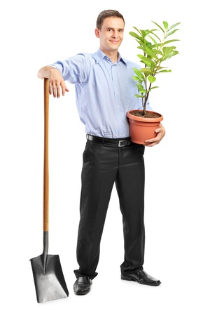 Full length portrait of a smiling man holding a plant and a shovel isolated on white background photo