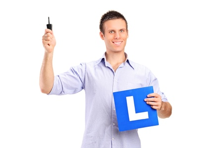 Happy man holding a car key and L plate isolated against white background Stock Photo - 10920878