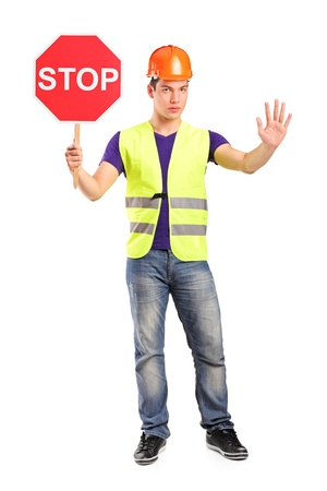 Full length portrait of a construction worker holding a traffic sign stop isolated on white background Stock Photo - 10920876