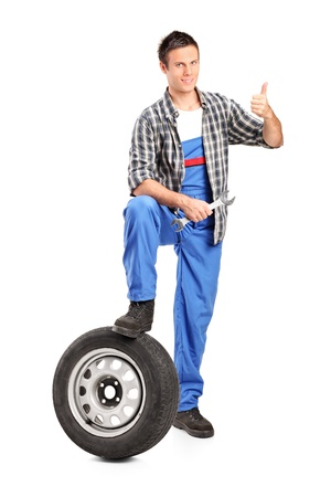 A smiling mechanic giving a thumb up with a spare tire and wrench isolated on white background Stock Photo - 11005112
