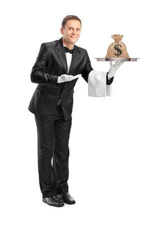 Full length portrait of a butler with bow tie holding a tray with a money bag on it isolated against white background photo