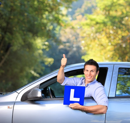 Happy male in his car holding a  L sign and giving thumb up after having his driver Stock Photo - 11005116
