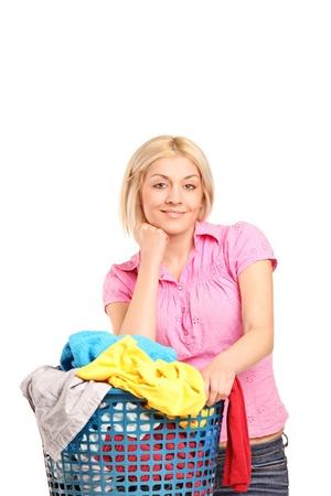 lavadora con ropa: Una mujer sonriente posando con un cesto de la ropa aisladas sobre fondo blanco Foto de archivo