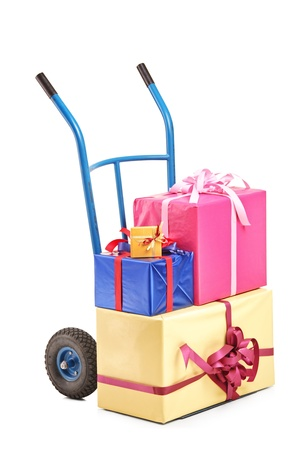 A studio shot of a hand truck with many gifts on it isolated against white background photo