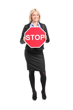 woman stop: Full length portrait of a businesswoman holding a traffic sign stop isolated on white background