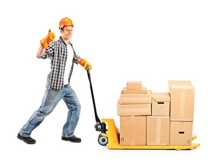 Full length portrait of a manual worker pushing a fork pallet truck stacker isolated on white background photo