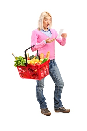 agitated: Full length portrait of a surprised woman looking at store receipt and holding a shopping basket isolated on white background