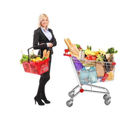 Full length portrait of a woman holding a shopping basket and shopping cart isolated on white background