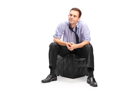 worried man: A studio shot of a disappointed businessman sitting isolated on white background