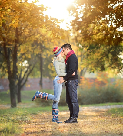 young couple hugging kissing: A view of a loving couple kissing in the park in autumn
