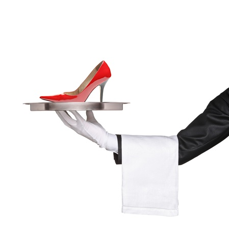 A waiter holding a silver tray with a red high heel on it isolated on white background photo