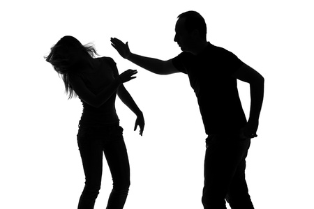 novios enojados: Silueta de un hombre golpeando a una mujer aislada contra el fondo blanco Foto de archivo