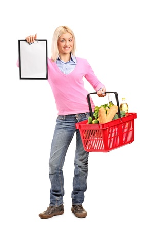 Full length portrait of a female holding a shopping basket and showing a clipboard isolated on white background photo