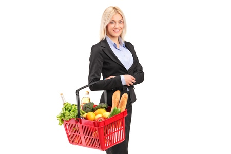 A young woman holding a shopping basket with groceries isolated on white background photo