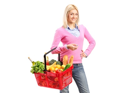 A young woman holding a full shopping basket isolated on white background photo