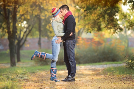 romantic kiss: Loving couple kissing in the park in autumn Stock Photo