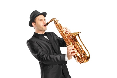 saxophonist: Studio portrait of a young man wearing hat and playing on saxophone isolated on background