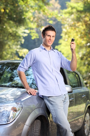 A smiling male holding a car key posing next to his automobile photo
