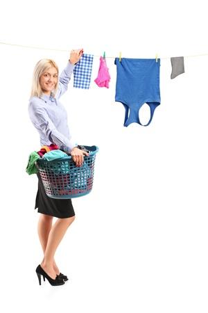 laundry: Retrato de cuerpo entero de una mujer joven y sonriente colgar la ropa en el tendedero con pinzas para la ropa aisladas sobre fondo blanco