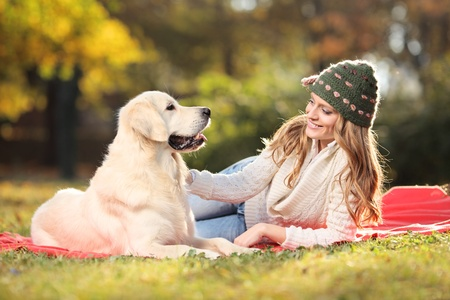 Girl playing with a labrador retriever dog in the park photo