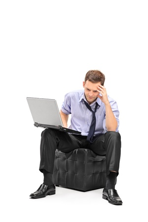 computer problem: A disappointed businessman working on his and his laptop isolated on white background